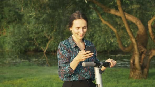Thumbnail for Portrait of attractive woman in shirt is using alternative electric scooter in park. E-transport