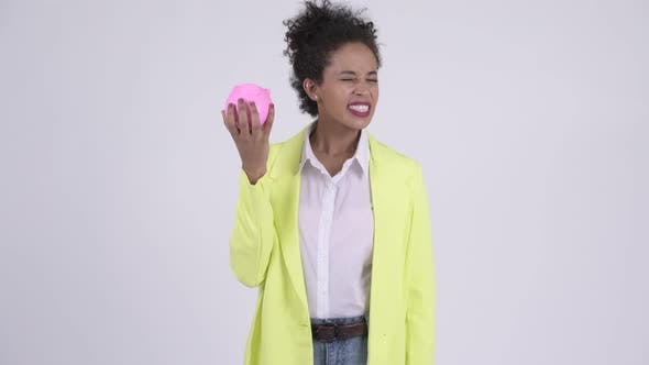Thumbnail for Young Stressed African Businesswoman Holding Piggy Bank and Giving Thumbs Down