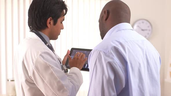 Thumbnail for Hispanic doctor using tablet pc to share MRI with patient