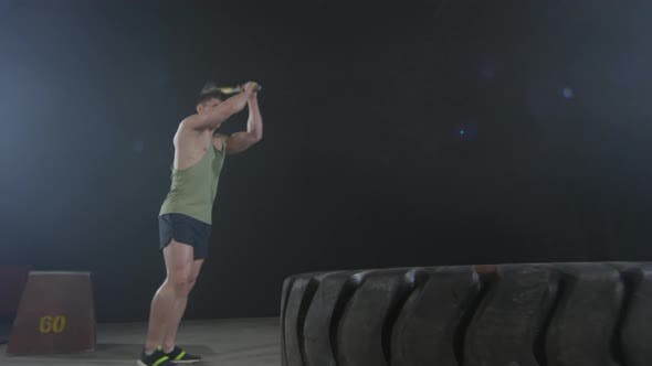 Thumbnail for Strong Sportsman Hitting Tire with Sledgehammer