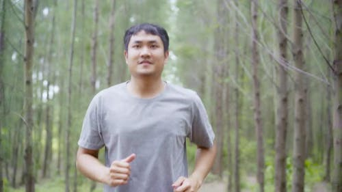 young athletic sporty Asian runner man in sports clothing running and jogging on forest trail.