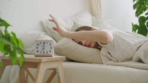 Morning of Sleepy Young Woman Turning Off Alarm Clock While Lying in Bed