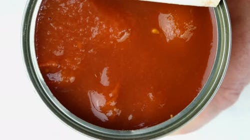 Hand Opens Metallic Tin Can of Tomatoes in Their Own Juice or Tomato Sauce