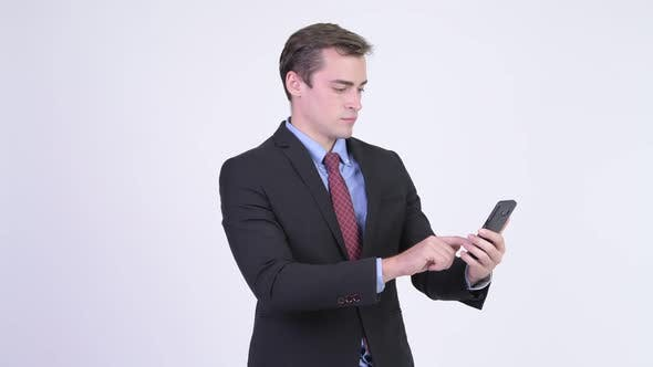Cover Image for Young Happy Handsome Businessman Using Phone and Getting Good News