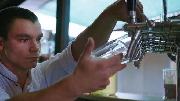 Thumbnail for Professional Bartender Pours Fresh Cool Light Draft Beer Into a Glass Using Pour From Keg