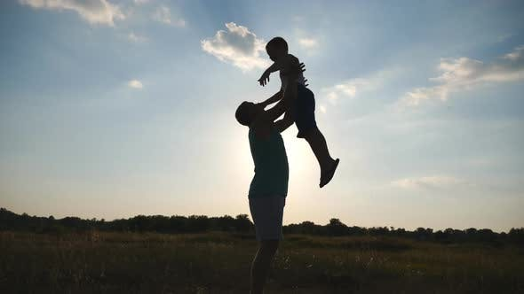 Thumbnail for Happy Daddy Throwing Up His Little Boy in the Air at Nature. Silhouettes of Father and Son Playing