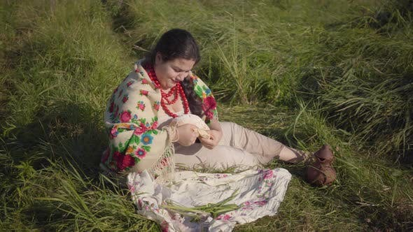 Thumbnail for Beautiful Overweight Woman Sitting in Grass on the Field Eating a Piece of Fresh Bread