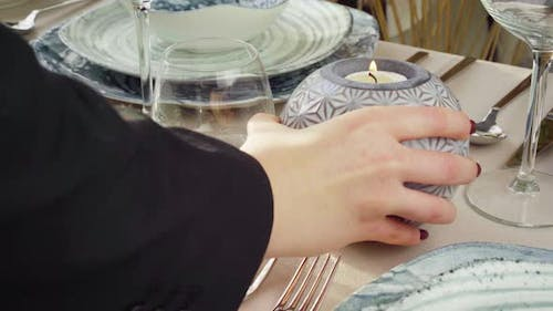 Close Up of Woman Putting Candle on Table