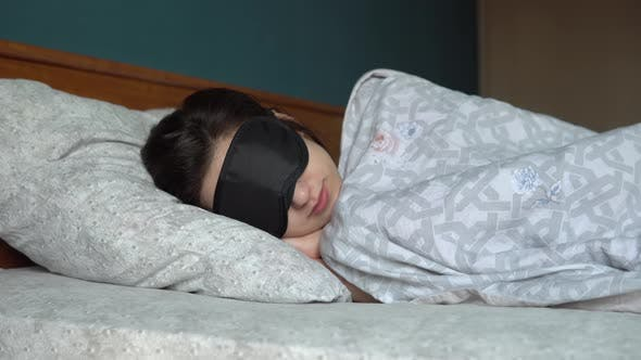 Thumbnail for A Young Woman Sleeps in a Sleep Mask. A Girl Lies in Bed in His Room