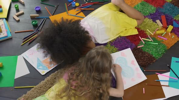 Thumbnail for Curly female kids lying on floor and drawing with color pencils at kindergarten