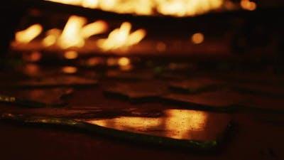 Flames reflected in broken glass
