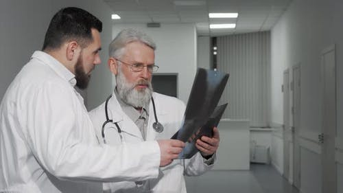 Two Male Doctors Discussing Xray Scans of a Patient at the Clinic