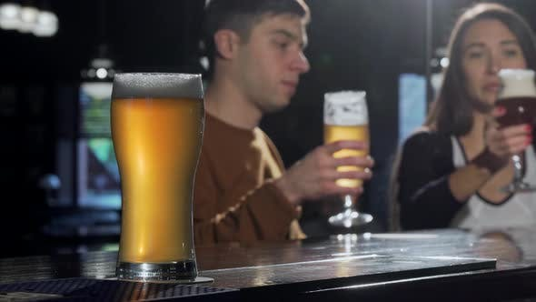 Thumbnail for Glass of Tasty Beer on Foreground, Couple Clinking Beers on the Back at the Pub