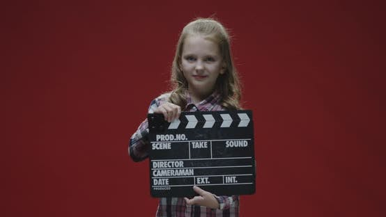 Girl Clapping Clapboard and Raising Eyebrows