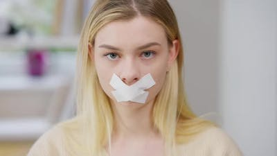 Closeup of Young Discriminated Woman with Taped Mouth Looking at Camera