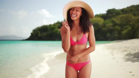 Mixed race woman smiling wearing a bikini on a beach