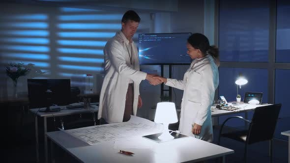 Two Diverse Scientists Giving Hands in Greeting on the Meeting in Lab