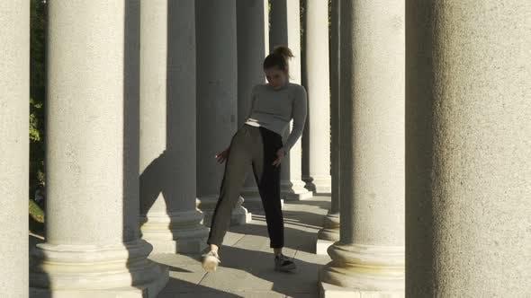young group dancing choreography between tall columns