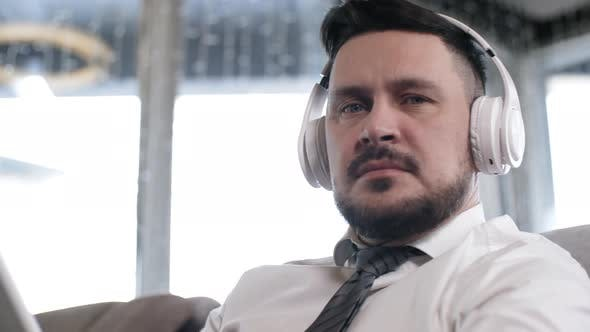 Cover Image for Portrait of Businessman in Wireless Earphones