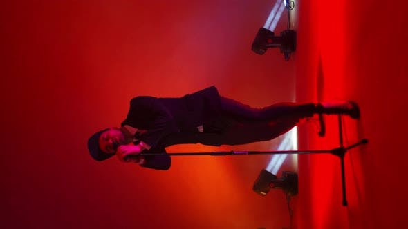 Thumbnail for Vertical Video. A Male Singer with a Microphone Stand Dances and Sings in the Neon Light in the