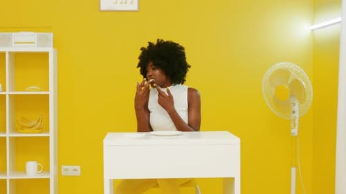 Woman Is Eating Pizza In Yellow-White Room
