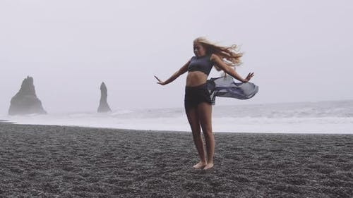 Passionate Young Dancer By the Black Beach on a Windy Day