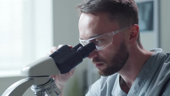 Thumbnail for Male Scientist Looking through Microscope in Laboratory