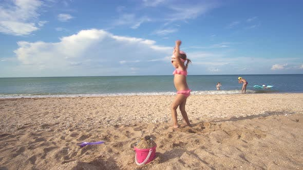 Thumbnail for Little Baby Girl In A Bathing Suit And Sunglasses On Playing Sandy Beach On Background