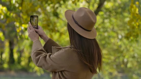 Thumbnail for Pretty Brunette Caucasian Girl in Brown Hat and Coat Taking Photos of Autumn Park on Her Smart Phone