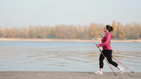 Thumbnail for Nordic Walking activity. Young cute woman walking in the city with nordic walking poles along river