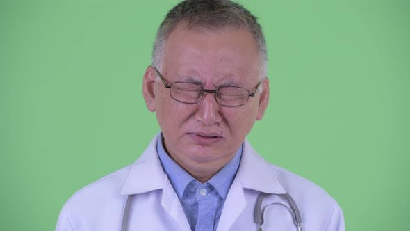 Thumbnail for Face of Stressed Mature Japanese Man Doctor Looking Sad and Crying