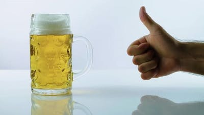 A Man Recommends Drinking Beer Pointing His Finger Up, Light Beer On A White Background