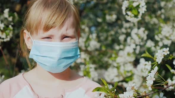 Portrait of a Child in a Gauze Bandage Against the Background of Flowering Trees
