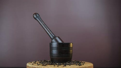 Spice mortar and pestle with spicy black pepper and clove