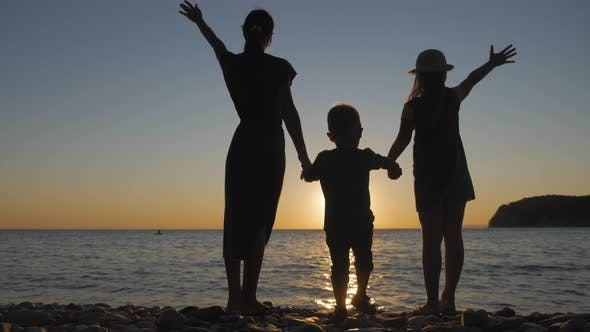 Happy Family Mother with Two Children on Vacation at the Beach. Silhouette Mother with Two Children