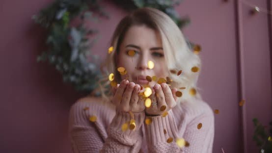 Thumbnail for Beautiful Woman in Sweater Blows Shiny Confetti From Her Hands To the Camera in Slow Motion
