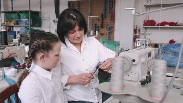 Thumbnail for Grandma with Little Granddaughter Sew Clothes in the Factory