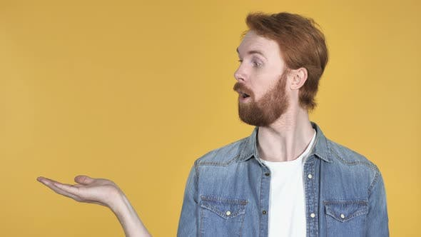 Thumbnail for Redhead Man Showing Product at Side Yellow Background