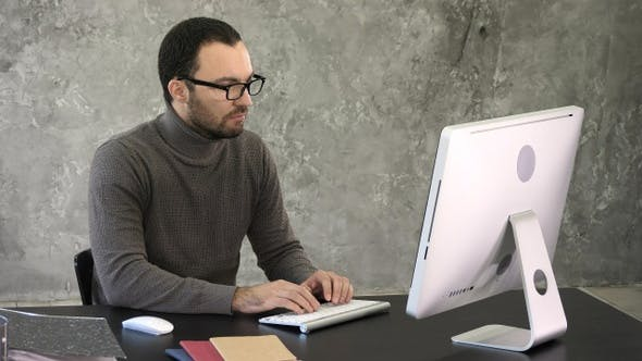 Thumbnail for Handsome businessman working on computer in office.
