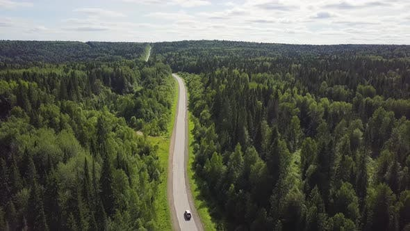 Thumbnail for Aerial View Of White Car Driving On Country Road In Forest