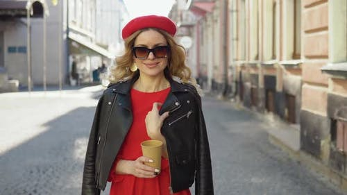 Woman in Red and Black Clothes in Glam Rock Style Posing in Front of the Camera with a Disposable