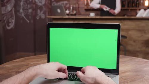 Parallax POV Shot of Person Typing on the Laptop with Green Screen on