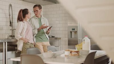 Couple Using Smartphone in Kitchen