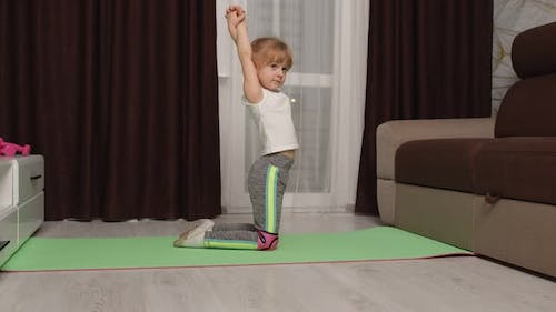 Girl Kid Girl Doing Gymnastics Stretching Workout at Home Watching Online Lessons on Laptop Pc