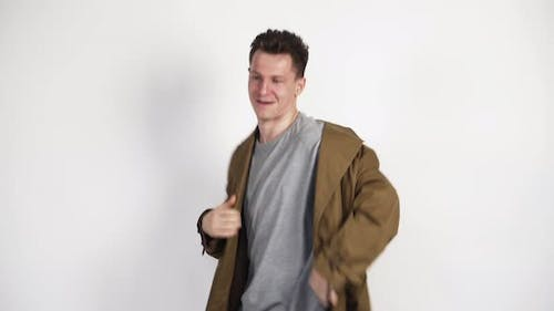 White Guy in a Brown Coat and a Funny Dance on a White Background. In a Good Mood. Positive Video.