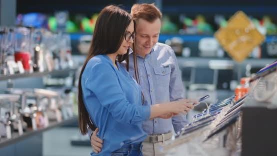 Thumbnail for Happy Couple Looking at a New Digital Camera at an Electronics Shop