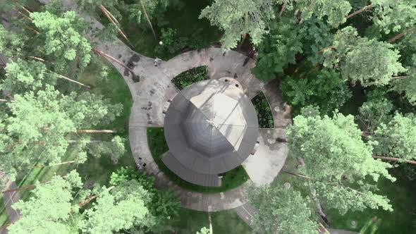 Beautiful christian domed church in green trees in city park at sunny day, top drone view
