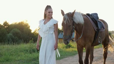 Lady Brunette with Long Hair in Ponytail Wanders with Horse