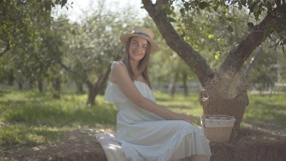 Niedliche junge Frau in Strohhut und lange weiße Kleid Blick auf die Kamera Lächeln sitzen