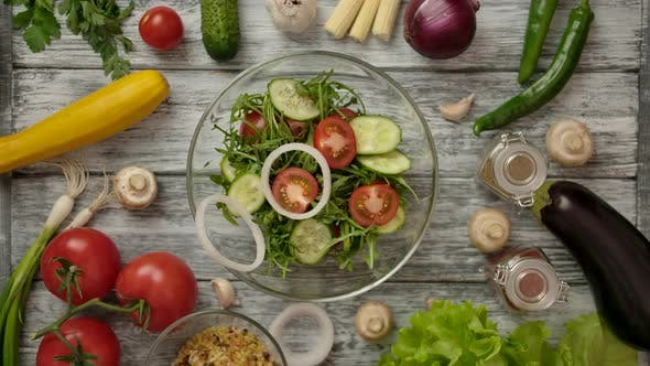 Thumbnail for Person Serving Salad with Onion Rings on Table with Ingredients